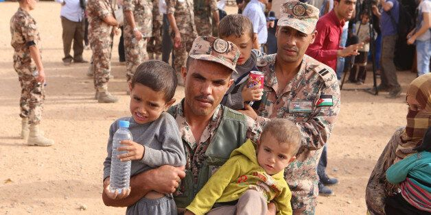 In this Thursday, Sept. 10, 2015 photo, a Jordanian soldier carries Syrian refugee children after they into Jordanian territo