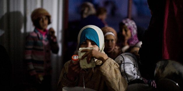 FILE - In this file photo taken Sunday, Dec. 9, 2012, Syrian girls wait for food distribution at a refugee camp near the Turk