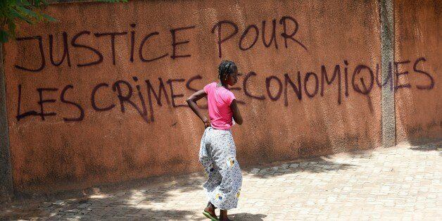 A woman walks past a wall with graffiti reading 'Justice for the economic crimes' in Ouagadougou on October 1, 2015. General