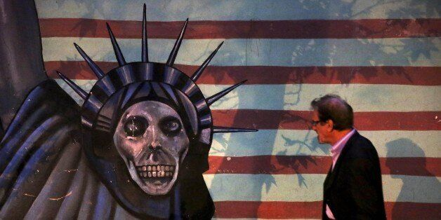 A man walks past a satirized painting of the Statue of Liberty painted on the wall of the former U.S. Embassy, in Tehran, Ira