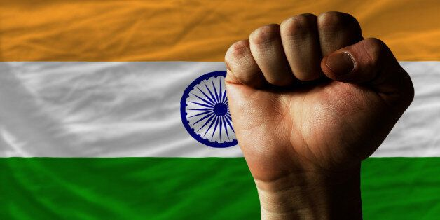 complete national flag of india covers whole frame, waved, crunched and very natural looking. In front plan is clenched fist