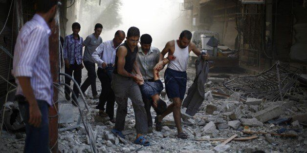 Syrians carry a wounded man following reported air strikes by Syrian government forces on the rebel-held town of Douma, east