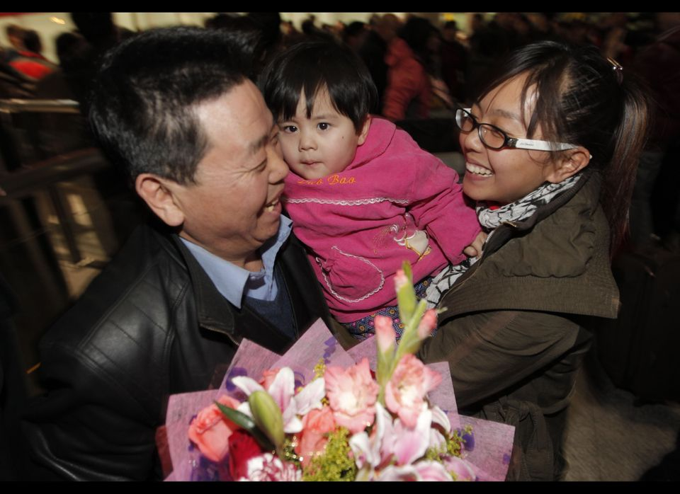 A Chinese worker, who was evacuated from Libya reacts with family members after arriving, at Beijing Capital International Ai