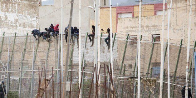 Would-be immigrants sit atop a border fence after attempting to cross from Morocco to the Spanish enclave of Melilla on Febru