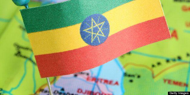 Ethiopian flag over cheap plastic map pointing Addis Abeba. Shallow depth of field
