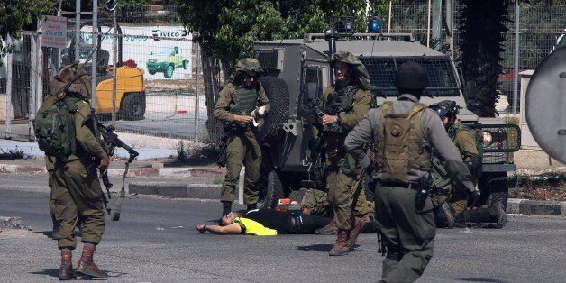 Israeli security forces stand next to the body of a Palestinian man who carried out a stabbing attack against an Israeli sold