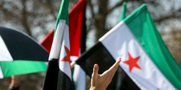 Human hand waving in front of Syrian flags.
