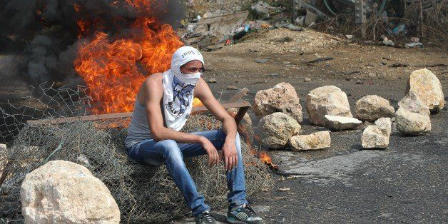 A Palestinian student from Palestine Polytechnic University sits during a protest against Israel near the Jewish settlement o