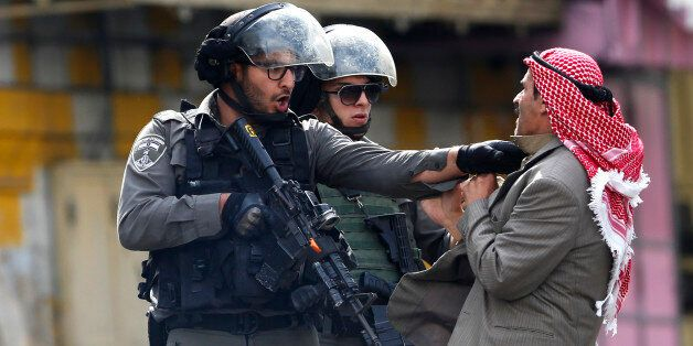 A Palestinian is pushed an Israeli policemen amid clashes in Hebron, West Bank, Saturday, Oct. 10, 2015. A Palestinian teenag