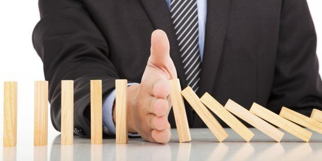 businessman hand stop dominoes continuous toppled on the desk