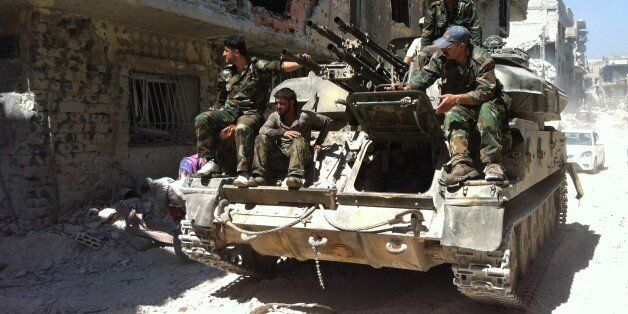 A picture taken on July 29, 2013 shows soldiers loyal to the regime forces sitting on a tank as they patrol in a devastated s