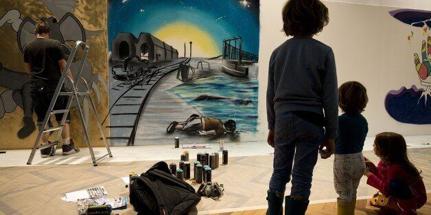 Children look at the art work 'Ni frontiere, ni souffrance' (No border, no pain) by French street artist MG La Bomba (unseen)