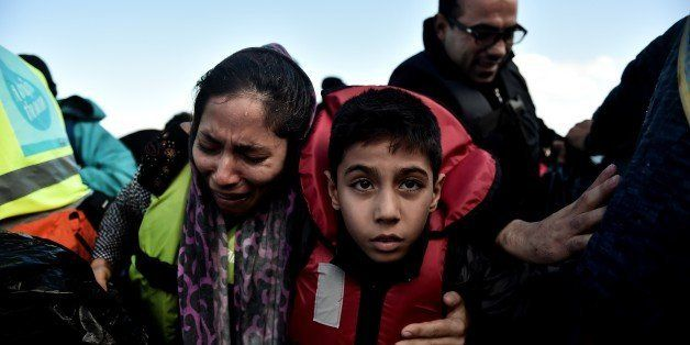 A woman, holding her child, cries as she arrives, with other refugees and migrants on the Greek island of Lesbos on October 2