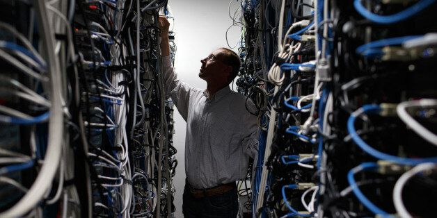 FILE PHOTO: An employee checks cabling on data storage devices in the computer data center at the head office of Alcatel-Luce