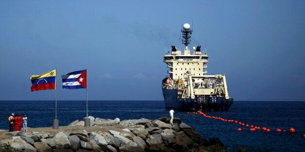 FILE - In this Jan. 22, 2011 file photo, people stand on a breakwater, with a Venezuelan flag, left, and a Cuban flag, as a s