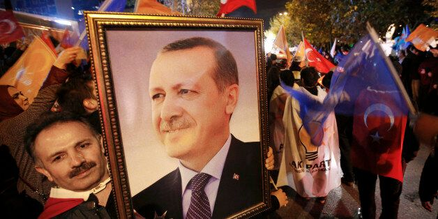 A supporter of the Justice and Development Party, (AKP), holds a portrait of Turkey's President Recep Tayyip Erdogan as peopl
