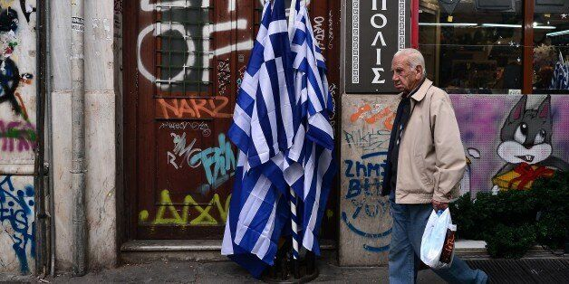 An elderly  man walks past Greek flags on sale in central Athens, on October 29, 2015.  The government is under increased pre