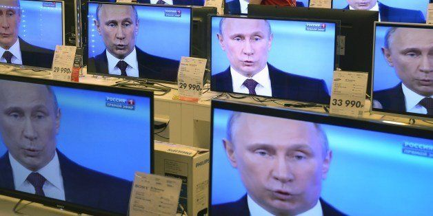 An employee walks past TV screens in a shop in Moscow, on April 17, 2014, during the broadcast of President Vladimir Putin's