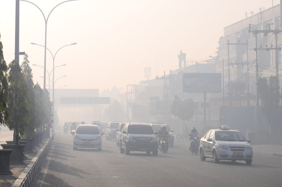 Commuters travel on a road blanketed by haze due to nearby forest fires, in Pekanbaru city, capital of Riau province on Sumat
