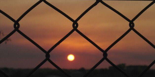Picture of a sunset behind bars