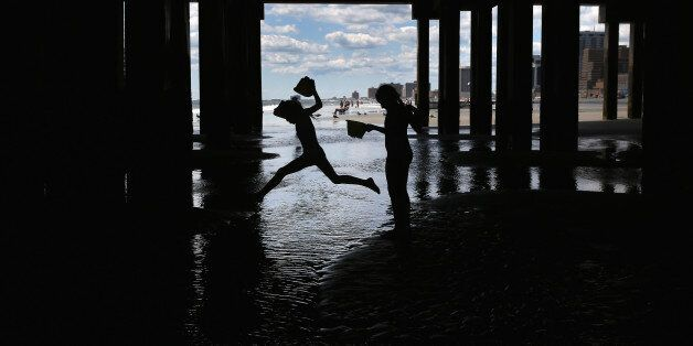 ATLANTIC CITY, NJ - AUGUST 28:  Children play under a pier near the closed Trump Plaza hotel on August 28, 2015 in Atlantic C