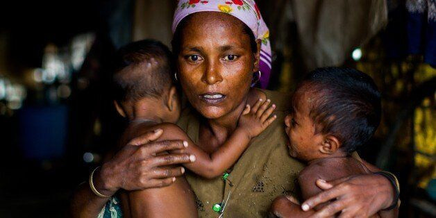 SITTWE , MYANMAR - JULY 17 : A distressed mother named Shamijder (age 30) holds onto her twins aged 1 year whom both suffer f
