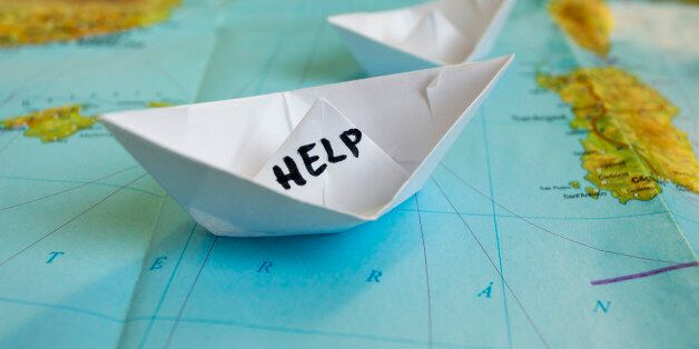 White paper boat onto world map with 'Help' sign on it.