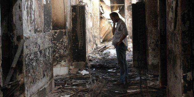In this Friday, Oct. 16, 2015 photo, an employee of Doctors Without Borders walks inside the charred remains of their hospita