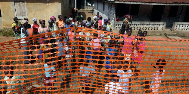 In this photo taken Friday, Aug. 14, 2015, people wait to be released from Ebola quarantine by Sierra Leone President Ernest