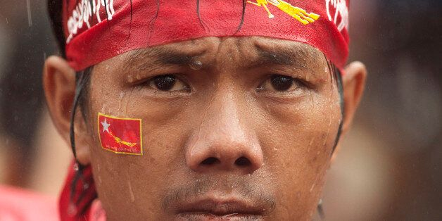 A supporter of Myanmar's National League for Democracy party waits in pouring rain outside the NLD headquarters in Yangon, My