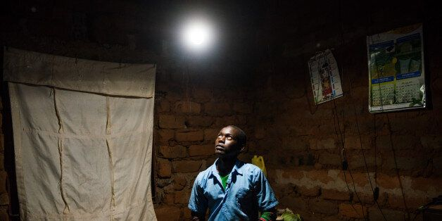 Erasmus Wambua, a schoolboy, looks at a single electric lightbulb, powered by M-Kopa solar technology, as it illuminates his