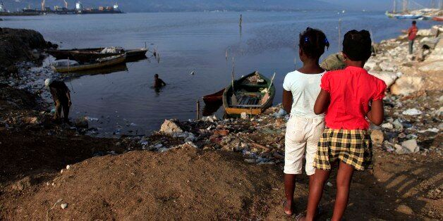 Two girls look at the harbor bay in Port-au-Prince, Haiti, Saturday, Oct. 24, 2015. More than 5½ years since Haiti suffered