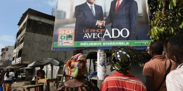 Two women look at a campaign poster that reads, 'The RHDP is with the ADO togther we can succeed' ('ADO' for Alassane Dramane