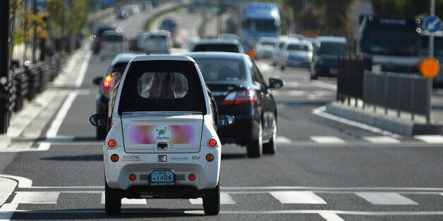 A Toyota Auto Body Co. Coms super-compact electric vehicle (EV) drives along a road in the Higashiyama district of Toyota Cit