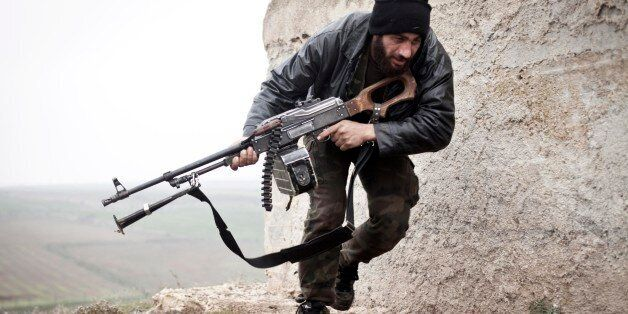 FILE - In this December 17, 2012 file photo, a Free Syrian Army fighter takes cover during fighting with the Syrian Army in A