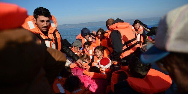 Migrants and refugees arrive on the Greek island of Lesbos after crossing the Aegean Sea from Turkey on November 18, 2015.  L