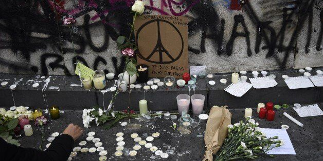 People law flowers and light candles at the Place de la Republique square in Paris on November 14, 2015, following a series o
