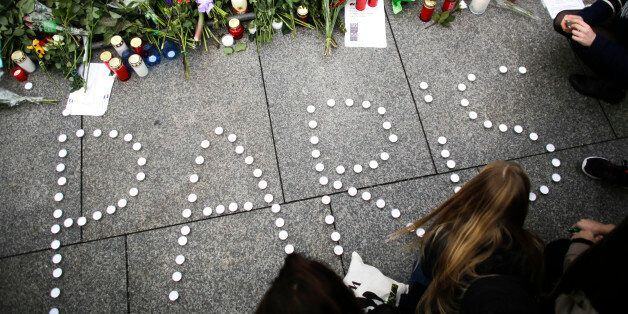 Young women have formed  the word Paris with candles to mourn for the victims killed in  Friday's attacks in Paris, France, i