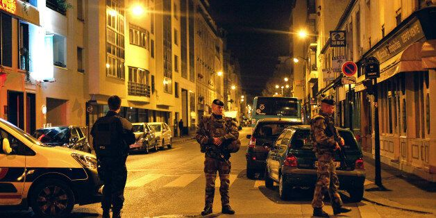 French soldiers and a police officer stand on a street next to Rue de Charonne, in Paris, Saturday, Nov. 14, 2015. The sidewa