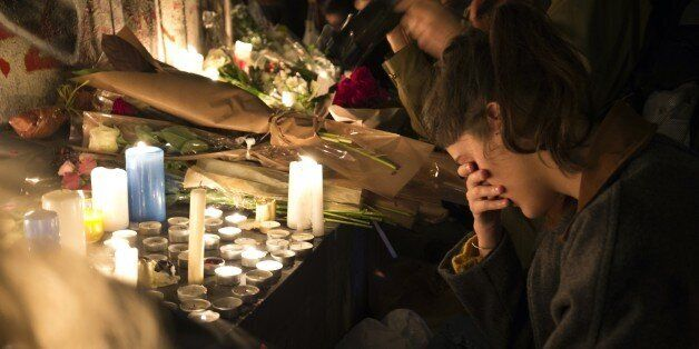 A woman reacts in front of candles in tribute to the victims of the deadly Paris' attacks on November 14, 2015 at the Place d