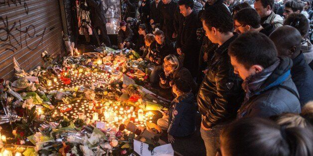 PARIS, FRANCE - NOVEMBER 14: Citizens who gathered around 'La Belle Equipe' leave flowers and light candles in front of the r