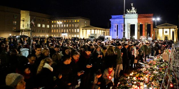 With the Brandenburg Gate, illuminated in the French national colors, in the background, people lay down flowers and light ca