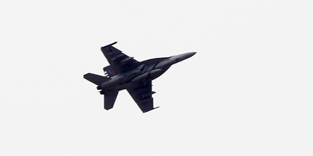 SANLIURFA, TURKEY -  OCTOBER 19:  (TURKEY OUT)  A fighter jet flies above the Syrian town of Kobani on October 19, 2014 in Sa