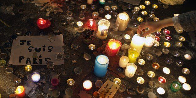 A person lights a candle on November 15, 2015 at a makeshift memorial in the 'Vieux port' of Marseille, for the victims of No