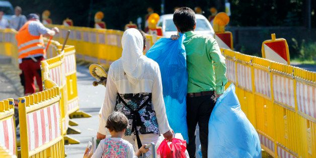 Asylum seekers walk outside the central refugee camp in Giessen, Germany, Monday, Aug. 3, 2015. (AP Photo/Michael Probst)