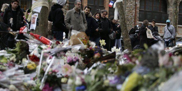 People spend a moment mourning the dead at the site of the attack at the Cafe Belle Equipe on rue de Charonne, prior to going
