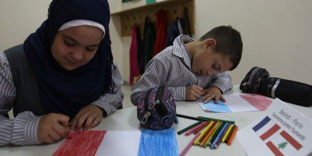 Children draw French flags at the Bahaa Al-Hariri school in the southern Lebanese city of Sidon on November 16, 2015. An even