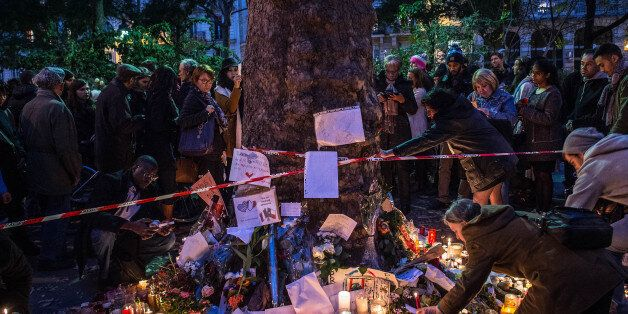 PARIS, FRANCE - NOVEMBER 16:  People place flowers and candles in memory of the victims of Friday's attack in front of Batacl