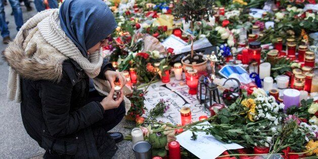 BERLIN, GERMANY - NOVEMBER 16:  A young Muslim woman lights a candle outside the French Embassy among candles, messages and f