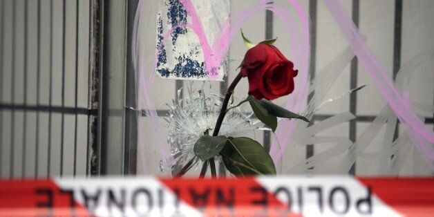 Flowers are put on bullet holes in the windows of the cafe 'Bonne biere', on November 17, 2015  in tribute to the victims of